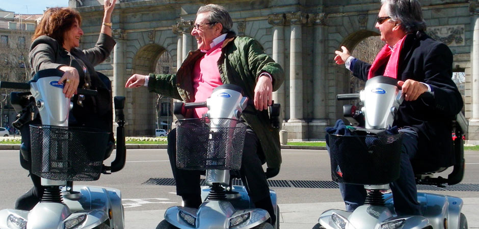 three people in mobility scooter with the door of Alcalá de Madrid background